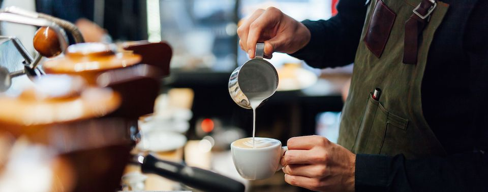 A barista pouring milk into a coffee cup.